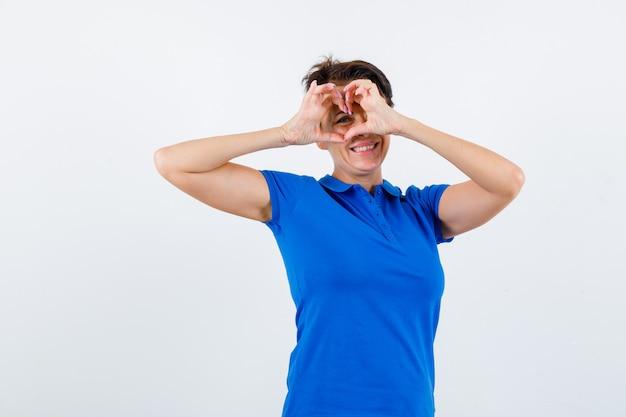 Rijpe vrouw in blauw t-shirt die hartgebaar toont en vrolijk, vooraanzicht kijkt.