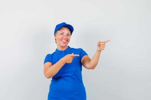 Rijpe vrouw in blauw t-shirt die naar de kant wijst en vrolijk kijkt.