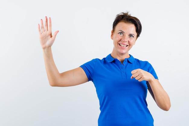 Rijpe vrouw in blauw t-shirt zwaaiende hand terwijl gebalde vuist en op zoek vrolijk, vooraanzicht.