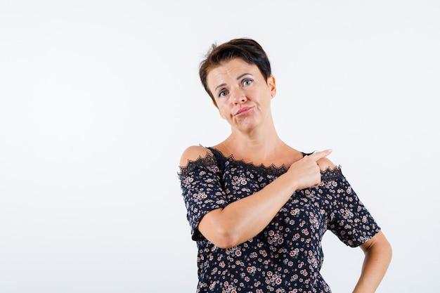 Rijpe vrouw in bloemenblouse, zwarte rok die met wijsvinger naar achteren wijst, hand op taille houdt en ernstig, vooraanzicht kijkt.