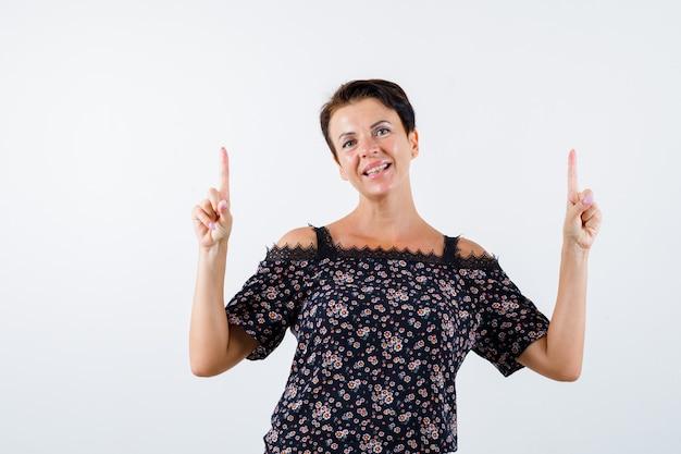 Rijpe vrouw in bloemenblouse, zwarte rok die met wijsvingers omhoog wijst en vrolijk, vooraanzicht kijkt.