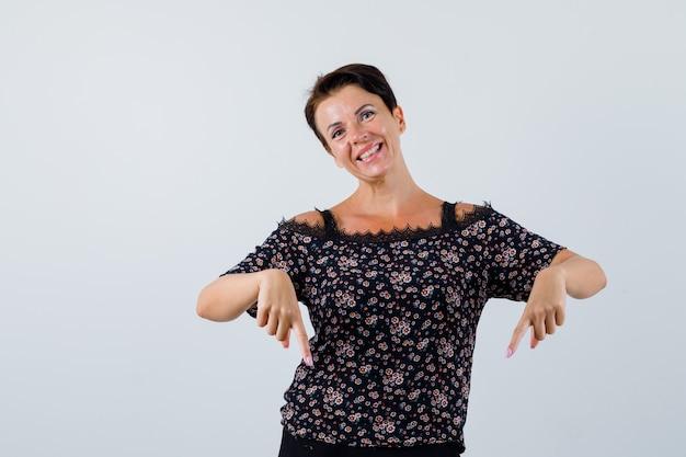 Rijpe vrouw in blouse die naar beneden wijst en gelukkig, vooraanzicht kijkt.
