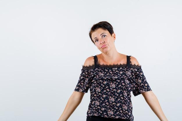 Rijpe vrouw in blouse die wapens opzij strekt en zelfverzekerd, vooraanzicht kijkt.