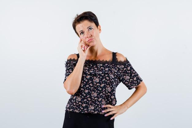 Rijpe vrouw in blouse die zich in denken stelt terwijl hand op taille wordt gehouden en besluiteloos, vooraanzicht kijkt.