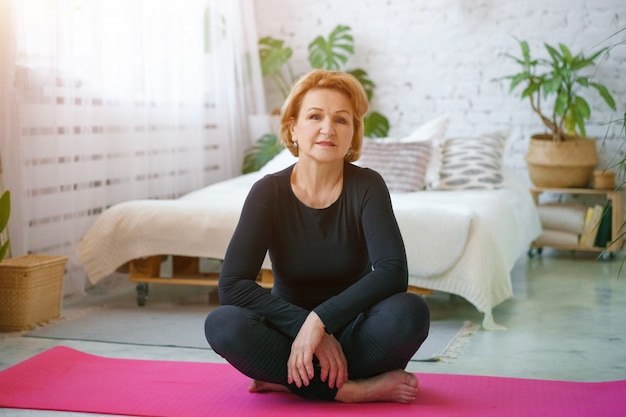 Rijpe vrouw in een zwart trainingspak yoga thuis zittend op de mat, tegen de achtergrond van een bed en potten met groene planten, gezonde levensstijl concept om thuis te zitten