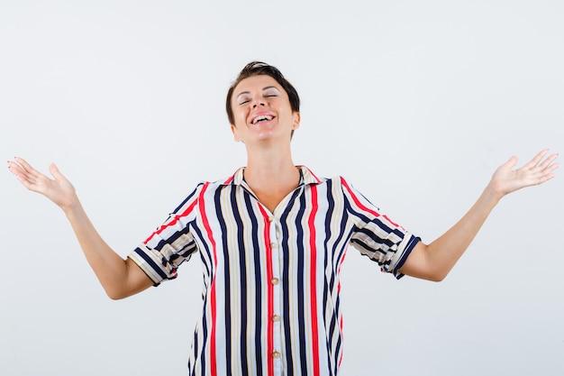 Rijpe vrouw in gestreepte blouse die hulpeloos gebaar toont en vrolijk, vooraanzicht kijkt.