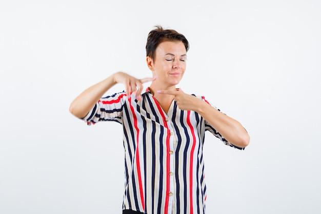 Rijpe vrouw in gestreepte blouse die tegengestelde richtingen richt, ogen sluit en kalm, vooraanzicht kijkt.