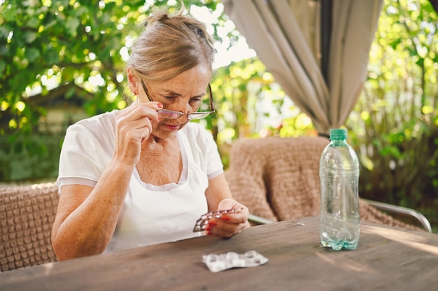 Rijpe vrouw in glazen houdt pillen lees medicijninstructie op verpakking voordat medicatie wordt ingenomen. bejaarde senior oude vrouw neemt vitamines buiten in de tuin. gezondheidszorg ouderen levensstijl concept