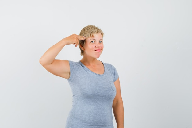 Rijpe vrouw in grijs t-shirt die zelfmoordgebaar imiteert en zelfverzekerd kijkt