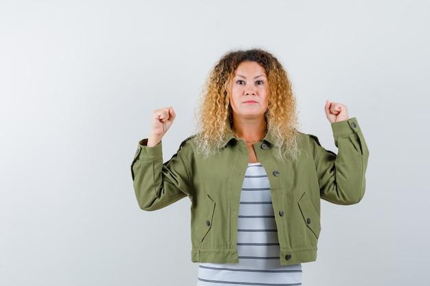Rijpe vrouw in groen jasje, t-shirt die winnaargebaar toont en zegevierend, vooraanzicht kijkt.