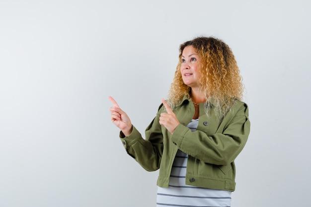Rijpe vrouw in groen jasje, t-shirt wijzend naar de linkerbovenhoek en kijkt vrolijk, vooraanzicht.