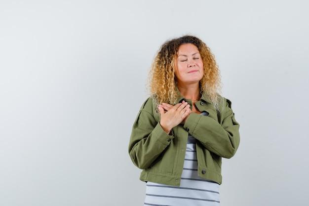 Rijpe vrouw in groene jas, t-shirt die handen op de borst houdt en ogen sluit en vredig, vooraanzicht kijkt.