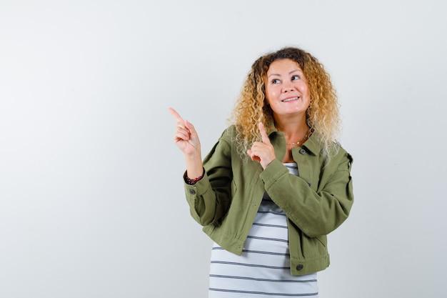 Rijpe vrouw in groene jas, t-shirt die omhoog wijst terwijl glimlachend en vrolijk, vooraanzicht kijkt.