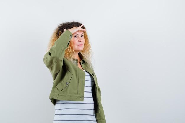 Rijpe vrouw in groene jas, t-shirt op zoek ver weg met hand boven het hoofd en op zoek gericht, vooraanzicht.