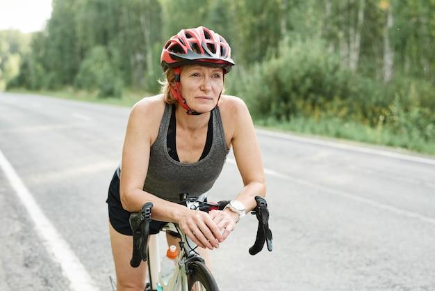 Rijpe vrouw in helm zittend op de fiets die deelneemt aan sportcompetitie buitenshuis