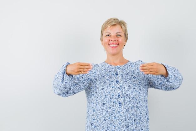 Rijpe vrouw in jurk gebaren met handen plat gehouden en op zoek gelukkig