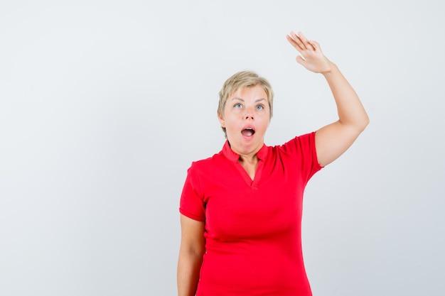 Rijpe vrouw in rode t-shirt die hand opheft om hoogte te tonen en verbaasd kijkt