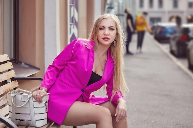 Rijpe vrouw in roze pak met lang blond haar zit op bankje in sint-petersburg, rusland.
