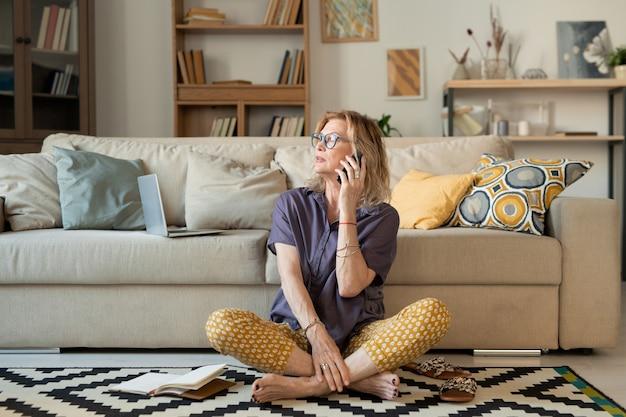 Rijpe vrouw in vrijetijdskleding zittend op een tapijt door bank met haar benen gekruist tijdens het gesprek met haar vriend of echtgenoot op smartphone