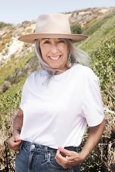 Rijpe vrouw in wit t-shirt en panamahoed voor zomerse buitenshoot
