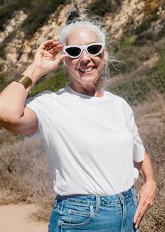 Rijpe vrouw in wit t-shirt voor buitenshoot in de zomer