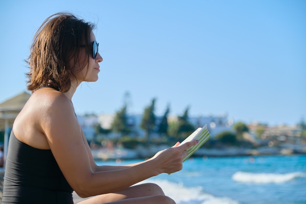 Rijpe vrouw in zonnebril zwembroek leesboek zittend op zand door zee. rust, vakantie, genieten van de natuur, zonnebaden bij zonsondergang, ruimte kopiëren