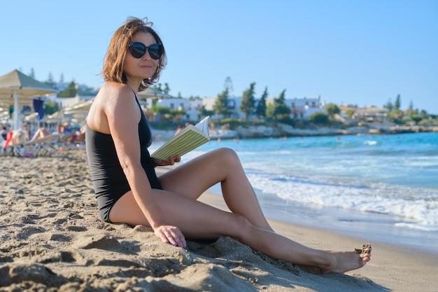 Rijpe vrouw in zonnebril zwembroek ontspannen leesboek genieten van zee zonsondergang. vrouw zittend op het zandstrand, zonnebaden in de avondzon, kopieer ruimte