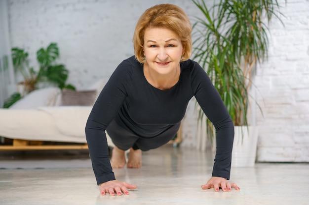 Rijpe vrouw in zwarte sportkleding die push-ups thuis doet. gezond levensstijlconcept