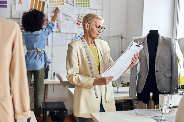 Rijpe vrouw kleermaker kijkt naar papieren terwijl afro-amerikaanse dame een foto op de muur zet