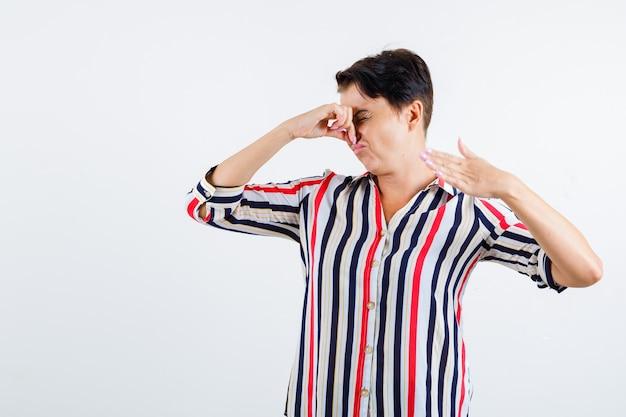 Rijpe vrouw knijpen neus als gevolg van slechte geur in gestreepte blouse en op zoek geïrriteerd. vooraanzicht.