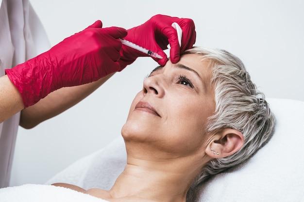 Rijpe vrouw krijgt verjongende gezichtsinjecties. ze ligt rustig in de kliniek. de deskundige schoonheidsspecialiste injecteert botox in de rimpels van de vrouw.