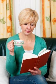 Rijpe vrouw leest een boek