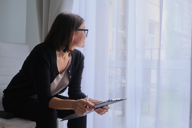 Rijpe vrouw maatschappelijk werker, psycholoog zit bij het raam met klembord.