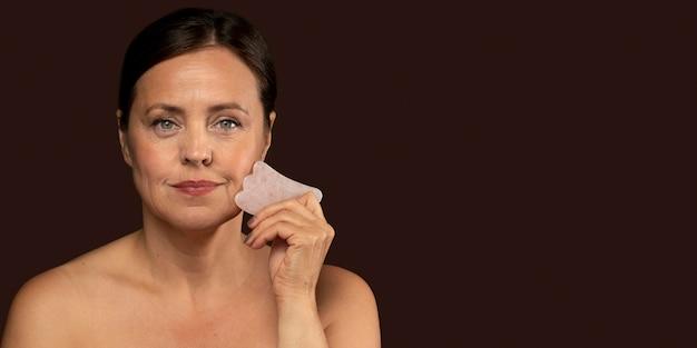Rijpe vrouw met behulp van rozenkwarts gezicht beeldhouwer met kopie ruimte