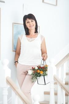 Rijpe vrouw met bloemen binnen. portret van medio volwassen vrouw met boquet van bloemen.