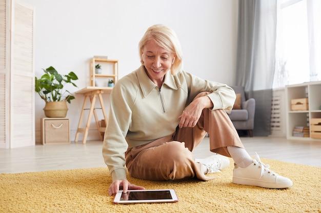 Rijpe vrouw met blonde haren zittend op de vloer en glimlachend kijkt ze naar iets op tablet pc in de kamer