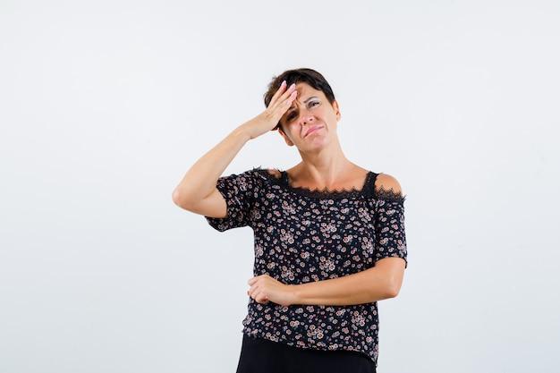 Rijpe vrouw met de hand op het voorhoofd, met hoofdpijn in bloemenblouse en zwarte rok en op zoek geïrriteerd. vooraanzicht.