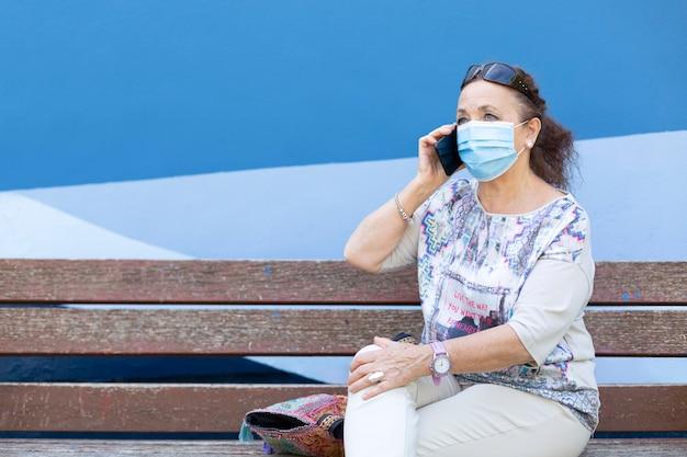 Rijpe vrouw met een medisch masker dat aan de telefoon spreekt.