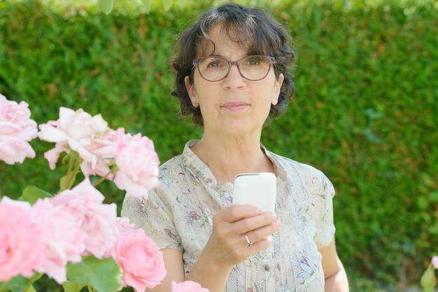 Rijpe vrouw met een telefoon in haar tuin