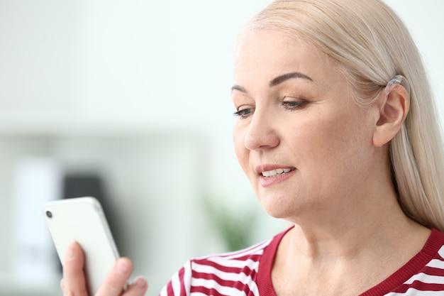 Rijpe vrouw met gehoorapparaat die mobiele telefoon thuis met behulp van