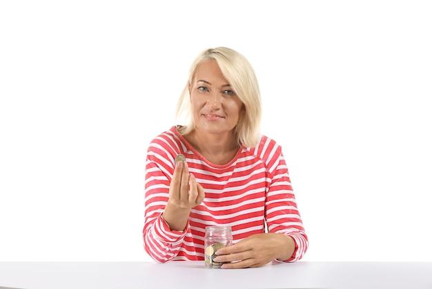 Rijpe vrouw met glazen pot met munten geïsoleerd