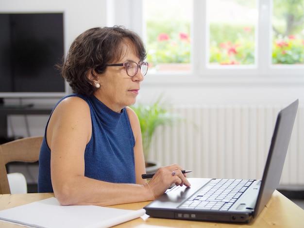 Rijpe vrouw met haar laptop in het huis
