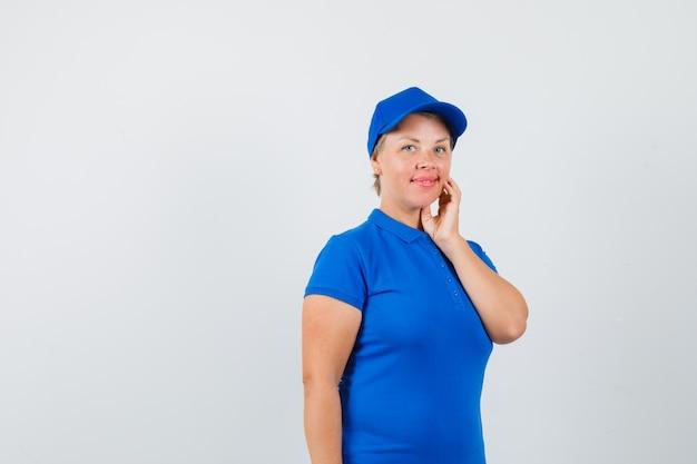 Rijpe vrouw met hand aanraken van wang in blauw t-shirt en op zoek schattig