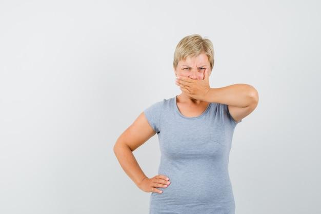 Rijpe vrouw met hand op mond in grijs t-shirt en koppig op zoek.