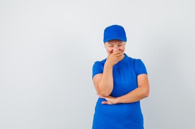 Rijpe vrouw met hand op mond terwijl lachen in blauw t-shirt