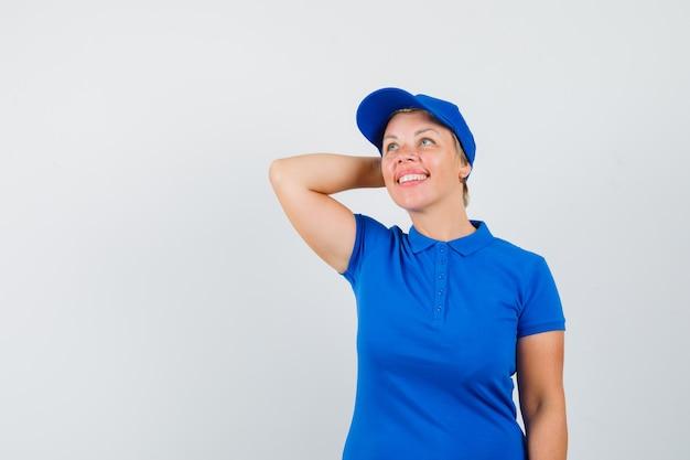 Rijpe vrouw met hand op nek in blauw t-shirt en dromerig op zoek.