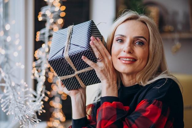 Rijpe vrouw met kerstmisgift door bthe venster
