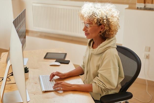 Rijpe vrouw met krullend haar zittend op haar werkplek en typen op computertoetsenbord en kijken naar computermonitor die ze met software werkt