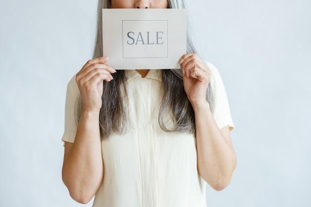 Rijpe vrouw met lang grijs haar houdt verkoopteken in studioclose-up