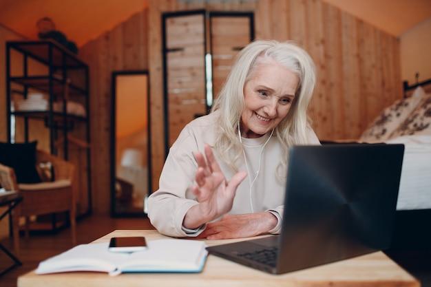 Rijpe vrouw met laptop aan tafel zitten en praten in glamping camping tent moderne vakantie lifes...